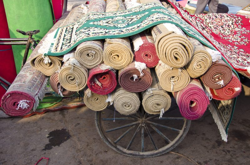 various colorful carpets rolls in Delhi market, India
